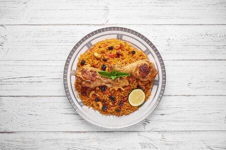 Chicken Kabsa or Chicken biryani at white wooden background. Kabsa is traditional saudi arabian cuisine dish. It cooks with basmati rice, chicken, spices, tomatoes, nuts, raisins. Copy space. Top view 版權商用圖片
