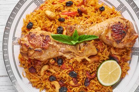 Chicken Kabsa or Chicken Biryani at white wooden background. Kabsa is traditional saudi arabian cuisine dish. Kabsa cooks with basmati rice, chicken, spices, tomatoes, nuts and raisins. Close up 版權商用圖片