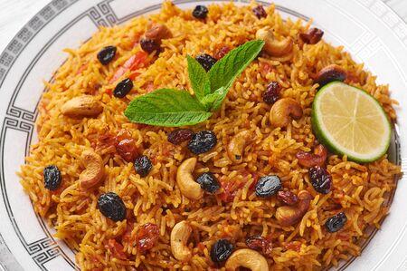 Vegetarian kabsa. Ramadan food. Kabsa is traditional saudi arabian cuisine dish. Kabsa cooks with basmati rice, spices, tomatoes, nuts and raisins. Close up