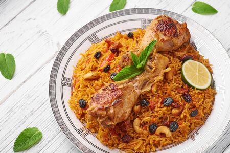 Chicken Kabsa oder Chicken Biryani auf weißem Holzhintergrund. Kabsa ist ein traditionelles saudi-arabisches Gericht. Kabsa kocht mit Basmatireis, Hühnchen, Gewürzen, Tomaten, Nüssen und Rosinen Textfreiraum