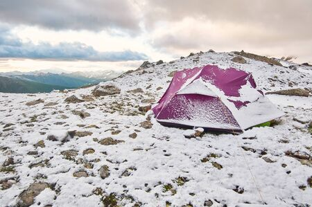 Purple tent under snow in the mountains. Trekking mountain camp concept Imagens