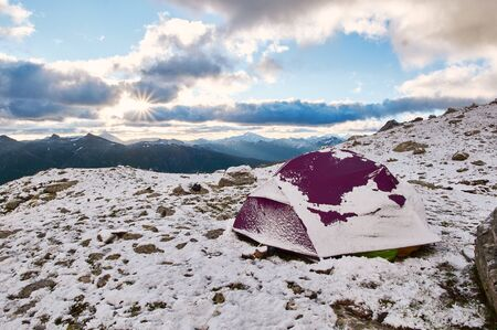 Purple tent under snow in the mountains. Trekking mountain camp concept Stockfoto
