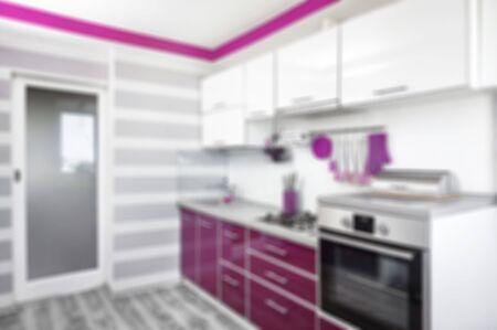 verschwommenes Kücheninterieur in lila, weißen und grauen Farben. Trendiges ultraviolettes Küchenraumdesign. Moderne Wohneinrichtung