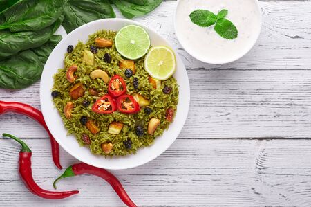 Palak Paneer Biryani and Raita at white wooden background with decor. Palak Paneer Biryani is vegetarian indian cuisine dish with spinach, paneer, basmati rice, spices, nuts and raisins. Copy Space