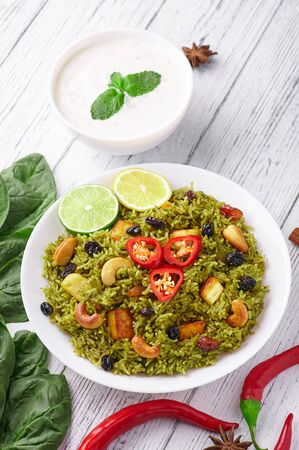 Palak Paneer Biryani and Raita at white wooden background with decor. Palak Paneer Biryani is vegetarian indian cuisine dish with spinach, paneer , basmati rice, spices, nuts and raisins. Vertical