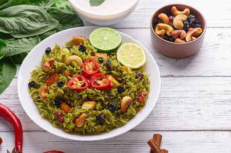 Palak Paneer Biryani and Raita at white wooden background with decor. Palak Paneer Biryani is vegetarian indian cuisine dish with spinach, paneer cheese, basmati rice, spices, nuts and raisins