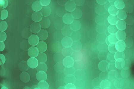 neo-mint bokeh of garland lights texture. abstract blurred background in trendy 2020 neo mint tones