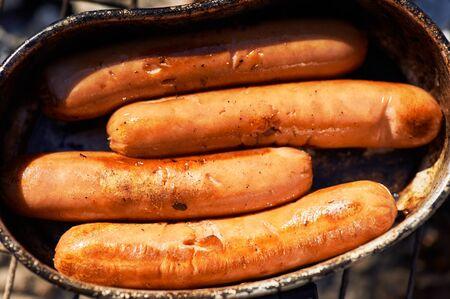 salchichas fritas en brasas de hoguera. cocinar en la fogata. Cocina de trekking o senderismo. De cerca Foto de archivo