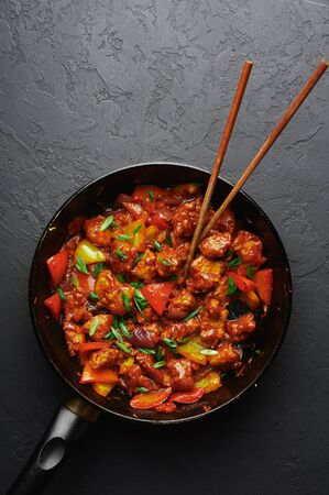 Chicken Manchurian in pan at black concrete background. Chicken Manchurian is Indian Chinese cuisine dish with Chicken breasts, bell pepper, tomatoes, soy sauce. Copy space