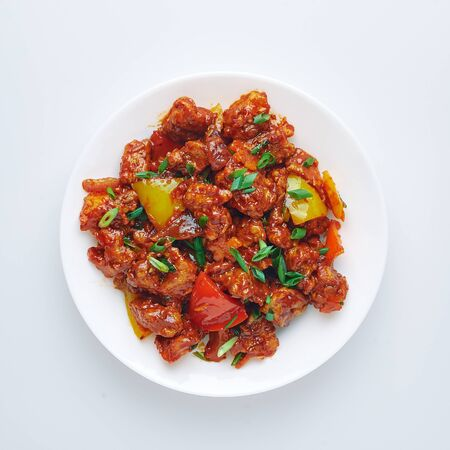 Chicken Manchurian isolated on white background. Chicken Manchurian is Indian Chinese cuisine dish with Chicken breasts, bell pepper, tomatoes, soy sauce. Isolate
