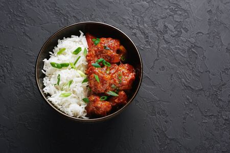 Chicken Manchurian in bowl with basmati rice at black concrete background. Chicken Manchurian is Indian Chinese cuisine dish with Chicken breasts, bell pepper, tomatoes, soy sauce. Copy space Stok Fotoğraf