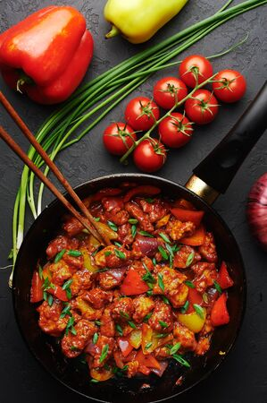 Chicken Manchurian in pan at black concrete background. Chicken Manchurian is Indian Chinese cuisine dish with Chicken breasts, bell pepper, tomatoes, soy sauce.
