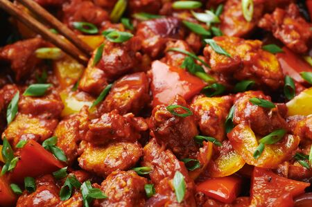 Chicken Manchurian at black concrete background. Chicken Manchurian is Indian Chinese cuisine dish with Chicken breasts, bell pepper, tomatoes, soy sauce.