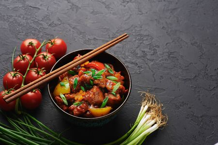 Chicken Manchurian in bowl at black concrete background. Chicken Manchurian is Indian Chinese cuisine dish with Chicken breasts, bell pepper, tomatoes, soy sauce. Copy space