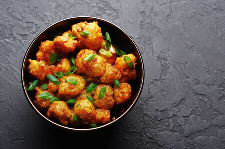 Gobi Manchurian in bowl at black concrete background. Gobi Manchurian is Indian Chinese cuisine dish with cauliflower, tomatoes, onion, soy sauce. Copy space