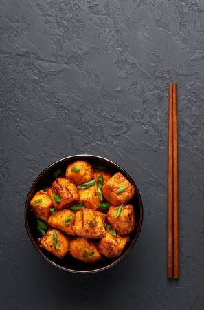 Paneer Manchurian or Paneer 65 in bowl at black concrete background. Paneer Manchurian is Indian Chinese cuisine dish with panner cheese, tomatoes, onion, soy sauce. Copy space. Stok Fotoğraf