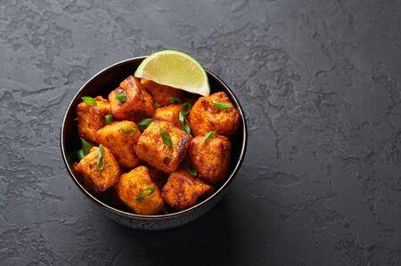 Paneer manchurian o Paneer 65 en un tazón con fondo de hormigón negro. Paneer manchurian es un plato de la cocina india china con queso panner, tomates, cebolla y salsa de soja. Copia espacio