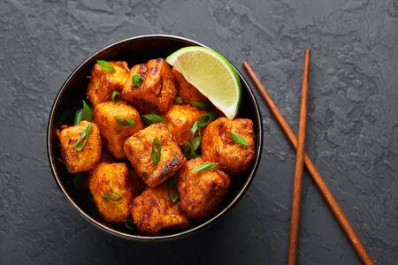 Paneer Manchurian or Paneer 65 in bowl at black concrete background. Paneer Manchurian is Indian Chinese cuisine dish with panner cheese, tomatoes, onion, soy sauce.