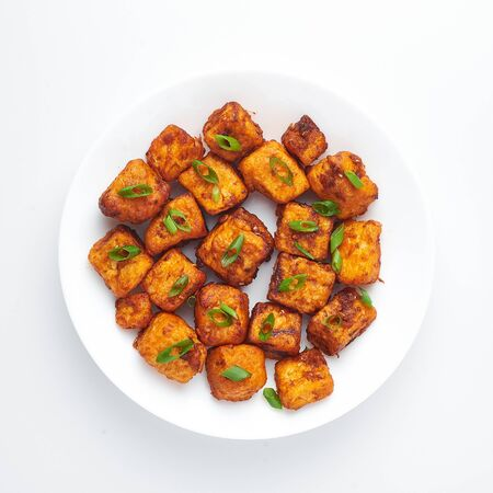 Paneer Manchurian or Paneer 65 isolated on white background. Paneer Manchurian is Indian Chinese cuisine dish with panner cheese, tomatoes, onion, soy sauce. Isolate