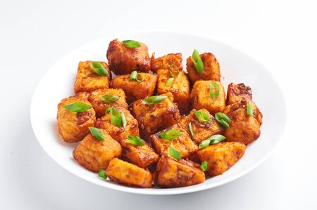 Paneer Manchurian or Paneer 65 isolated on white background. Paneer Manchurian is Indian Chinese cuisine dish with panner cheese, tomatoes, onion, soy sauce.