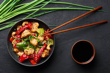 Schezwan Chicken or Dragon Chicken in black bowl at dark slate background. Szechuan Chicken is popular indo-chinese spicy dish with chilli peppers, chicken and vegetables. Stock Photo