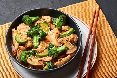 Hunan Chicken in black bowl at dark slate background. Hunan Chicken is chinese or indo-chinese cuisine takeaway dish with broccoli, zucchini, shiitake mushrooms and hunan sauce Reklamní fotografie