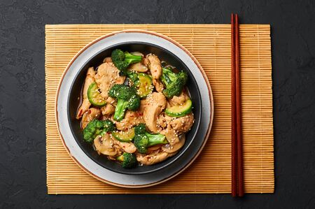 Hunan Chicken in black bowl at dark slate background. Hunan Chicken is chinese or indo-chinese cuisine takeaway dish with broccoli, zucchini, shiitake mushrooms and hunan sauce. top view