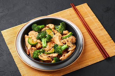 Hunan Chicken in black bowl at dark slate background. Hunan Chicken is chinese or indo-chinese cuisine takeaway dish with broccoli, zucchini, shiitake mushrooms and hunan sauce Banco de Imagens