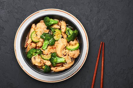 Hunan Chicken in black bowl at dark slate background. Hunan Chicken is chinese or indo-chinese cuisine takeaway dish with broccoli, zucchini, shiitake mushrooms and hunan sauce. Top view. Copy space Banco de Imagens