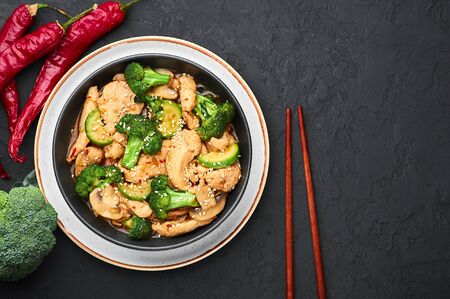 Hunan Chicken in black bowl at dark slate background. Hunan Chicken is chinese or indo-chinese cuisine takeaway dish with broccoli, zucchini, shiitake mushrooms and hunan sauce. Copy space Banco de Imagens