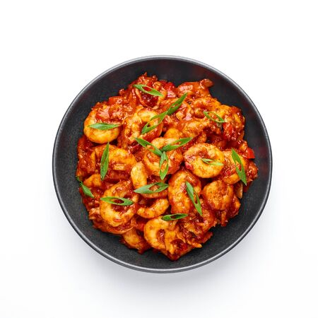 Schezwan Prawns isolated at white background. Schezwan Prawns is indo-chinese cuisine curry dish with prawns or shrimps roasted in Schezwan Sauce.