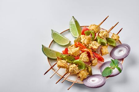 Chicken Tikka at skewers in white plate isolated at white background. Chicken tikka is an indian cuisine dish with grilled chicken meat with vegetables and spices. Indian food.