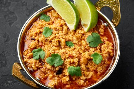 Chicken keema in traditional indian copper kadai at dark slate background. Kheema is indian and pakistani cuisine curry dish with minced meat and spices. Close up