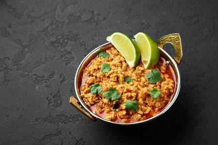 Chicken keema in traditional indian copper kadai at dark slate background. Kheema is indian and pakistani cuisine curry dish with minced meat and spices. Stock Photo