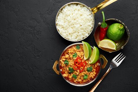 Chicken keema in traditional indian copper kadai at dark slate background. Kheema is indian and pakistani cuisine curry dish with minced meat and spices. Copy space. Top view