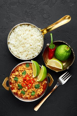 Chicken keema in traditional indian copper kadai at dark slate background. Kheema is indian and pakistani cuisine curry dish with minced meat and spices. Top view