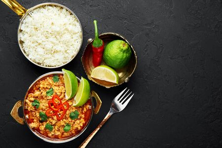 aChicken keema in traditional indian copper kadai at dark slate background. Kheema is indian and pakistani cuisine curry dish with minced meat and spices. Copy space. Top view