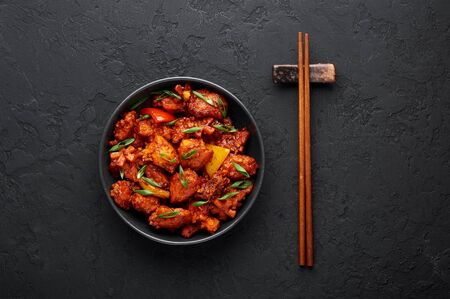 Fish Manchurian dry looks like Schezwan Fish in black bowl at dark slate background. Fish Manchurian - is indo chinese cuisine dish with deep fried salmon, bell peppers, sauce and onion. Top view