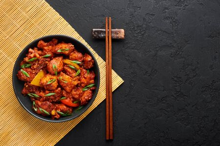 Fish Manchurian dry looks like Schezwan Fish in black bowl at dark slate background. Fish Manchurian - is indo chinese cuisine dish with deep fried salmon, bell peppers, sauce and onion. Top view.