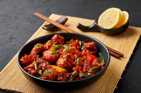 Fish Manchurian dry looks like Schezwan Fish in black bowl at dark slate background. Fish Manchurian - is indo chinese cuisine dish with deep fried salmon, bell peppers, sauce and onion.