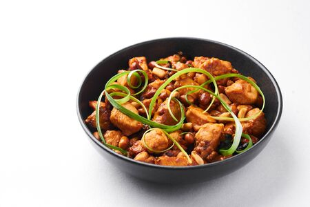 Kung Pao Chicken or Gong Bao Ji Ding isolated on white background. Sichuan Kung Pao is chinese cuisine dish with chicken meat, chilli peppers, peanuts, sauces and onion. Stock Photo