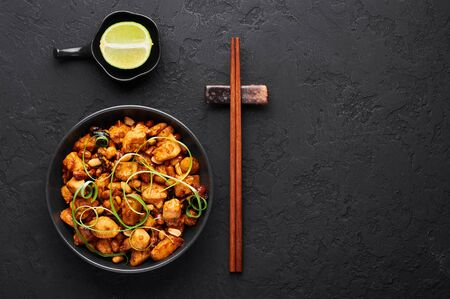 Kung Pao Chicken or Gong Bao Ji Ding at dark slate background. Sichuan Kung Pao is chinese cuisine dish with chicken meat, chilli peppers, peanuts, sauces and onion. Copy space. Top view