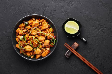 Kung Pao Chicken or Gong Bao Ji Ding at dark slate background. Sichuan Kung Pao is chinese cuisine dish with chicken meat, chilli peppers, peanuts, sauces and onion. Top view