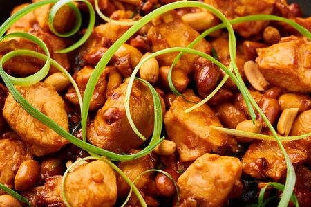 Kung Pao Chicken or Gong Bao Ji Ding at dark slate background. Sichuan Kung Pao is chinese cuisine dish with chicken meat, chilli peppers, peanuts, sauces and onion. Close up. Texture Stock Photo