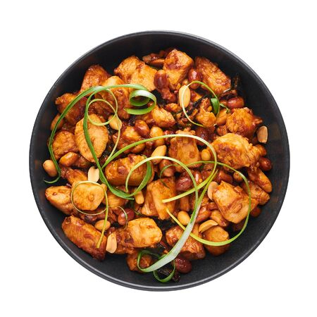 Kung Pao Chicken or Gong Bao Ji Ding isolated on white background. Sichuan Kung Pao is chinese cuisine dish with chicken meat, chilli peppers, peanuts, sauces and onion. Top view