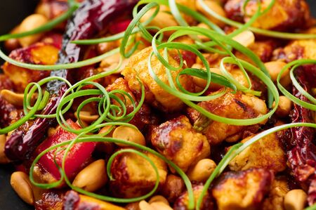 Kung Pao Paneer at black slate background. Kung Pao Paneer is a vegetarian version of chinese sichuan dish Gong Bao with paneer cheese, peanuts, chilli peppers, sauces and onion. Close up Stock Photo