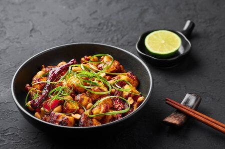 Kung Pao Paneer at black slate background. Kung Pao Paneer is a vegetarian version of chinese sichuan dish Gong Bao with paneer cheese, peanuts, chilli peppers, sauces and onion.
