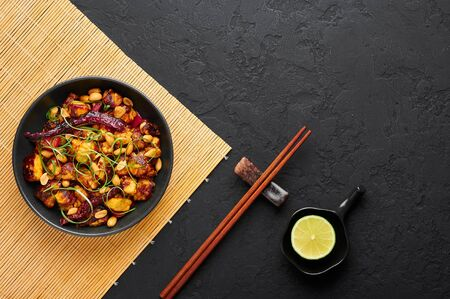 Kung Pao Paneer at black slate background. Kung Pao Paneer is a vegetarian version of chinese sichuan dish Gong Bao with paneer cheese, peanuts, chilli peppers, sauces and onion. Top view. Copy space
