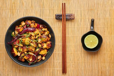 Kung Pao Paneer at black slate background. Kung Pao Paneer is a vegetarian version of chinese sichuan dish Gong Bao with paneer cheese, peanuts, chilli peppers, sauces and onion. Top view Stock Photo