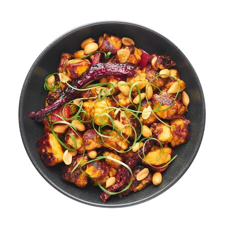 Kung Pao Paneer at isolated on white background. Kung Pao Paneer is a vegetarian version of chinese sichuan dish Gong Bao with paneer cheese, peanuts, chilli peppers, sauces and onion. Top view